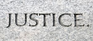 7400272-The-word-justice-carved-in-stone-Stock-Photo